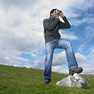 Man taking a picture with one foot on a rock