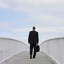 Businessman walking over a bridge