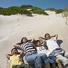 Family lying in the sand together