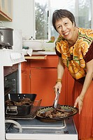 Woman putting cooked meat onto a plate