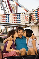 Women kissing either of a man´s cheeks on a roller coaster