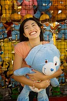 Young Asian woman holding stuffed animal at carnival