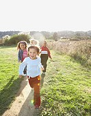 Group of children running through field