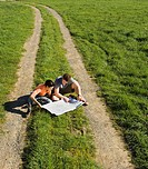 Couple reading a map on dirt trail
