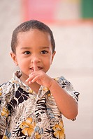 Young boy with finger over mouth