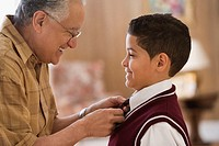 Older man tying grandson's school uniform tie