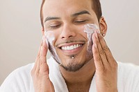 Young man spreading shaving cream on his cheeks