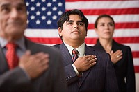 Businesspeople standing in front of an American flag with one hand across their hearts