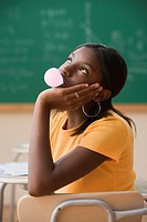 Bored student blowing a bubble gum bubble in class