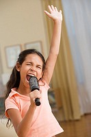 Young girl singing into a hairbrush