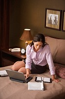 Businesswoman using a laptop in her hotel room