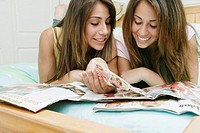 Teenage girls reading a magazine together