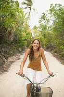 Young woman riding a bike on sandy path