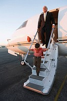 Businessman and young boy exiting a plane
