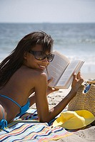 Rear view of a young woman reading on the beach (thumbnail)
