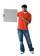 Young man pointing towards a blank sign (thumbnail)
