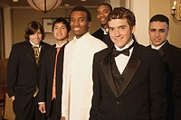 Teenage boys smiling for the camera at formal dance