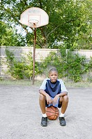 Young boy sitting on basketball