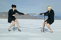 Two women in black costumes pulling rope, in desert