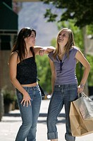 Two teenage girls (16-17) standing, laughing on sidewalk