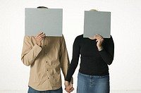 Couple holding hands and hiding faces with square cardboard pieces
