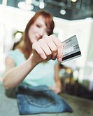 Young woman holding credit card (focus on credit card)