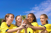 Four girls (11-17) in soccer uniforms holding trophy and cheering