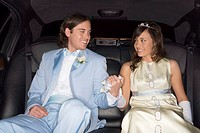Teenage boy and girl (14-16) in formalwear holding hands in limousine