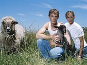 Young man and woman in field of tall grass with lamb and sheep