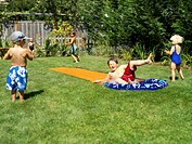 Five children (2-5) playing on water slide in yard, summer