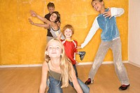 Five boys and girls (7-11) dancing in room