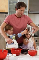 Father and son (5-7) sifting flour, daughter (2-4) sitting on worktop