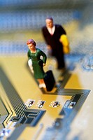 High angle view of the figurine of a woman and a man on a circuit board