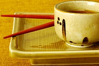 Close-up of a bowl of soy sauce with chopsticks on a serving tray