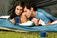 Close-up of a young woman and a mid adult man lying in a tent