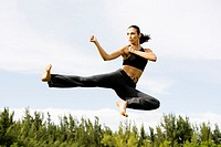Low angle view of a young woman practicing martial arts
