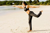 Young woman practicing martial arts on the beach