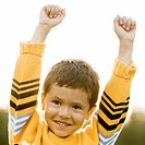 Close-up of a boy standing with his hands raised