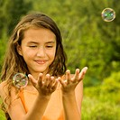 Close-up of a girl catching bubbles