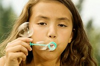 Close-up of a girl blowing bubbles with a bubble wand