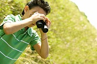 Close-up of a boy looking through a pair of binoculars