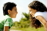 Close-up of a boy and a girl looking at each other smiling