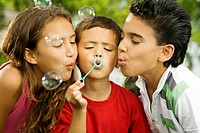 Close-up of two boys and a girl blowing bubbles with a bubble wand