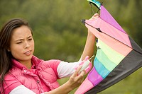 Close-up of a young woman holding a kite