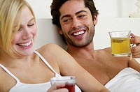 Couple sitting in bed, holding glass mugs, smiling, close-up