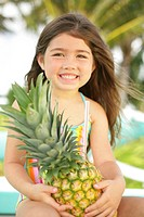 Girl (4-6) holding pineapple, smiling, portrait