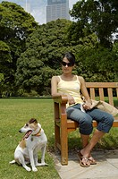 Young woman sitting on bench in park with jack russell terrier