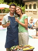 Couple holding glasses of white wine by bbq, portrait