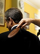 Barber brushing senior man´s shoulders, rear view