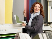 Woman looking at coloured paper in art shop, smiling